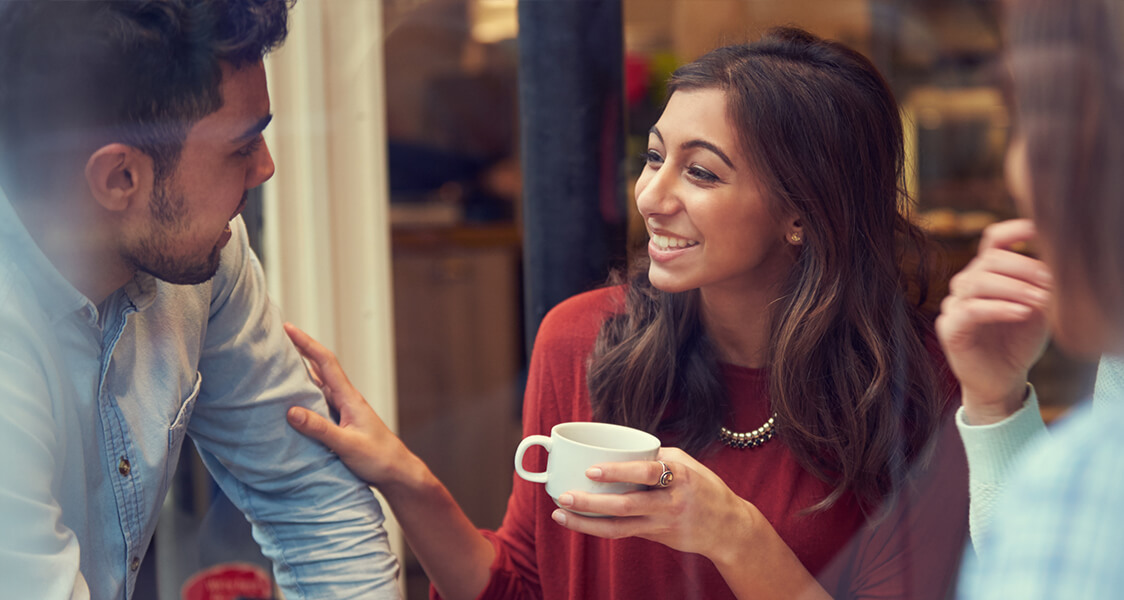 a man and a woman drinking coffee and smiling