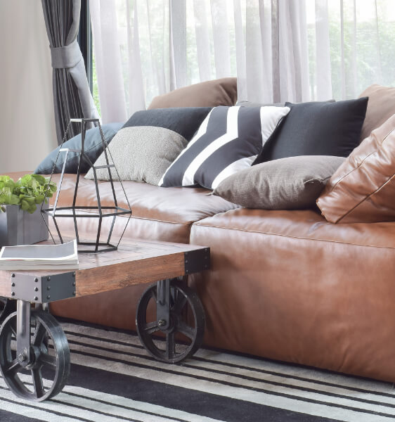 a brown couch with some accent pillows on it