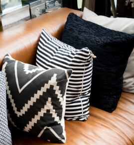 an assortment of pillows on a leather couch
